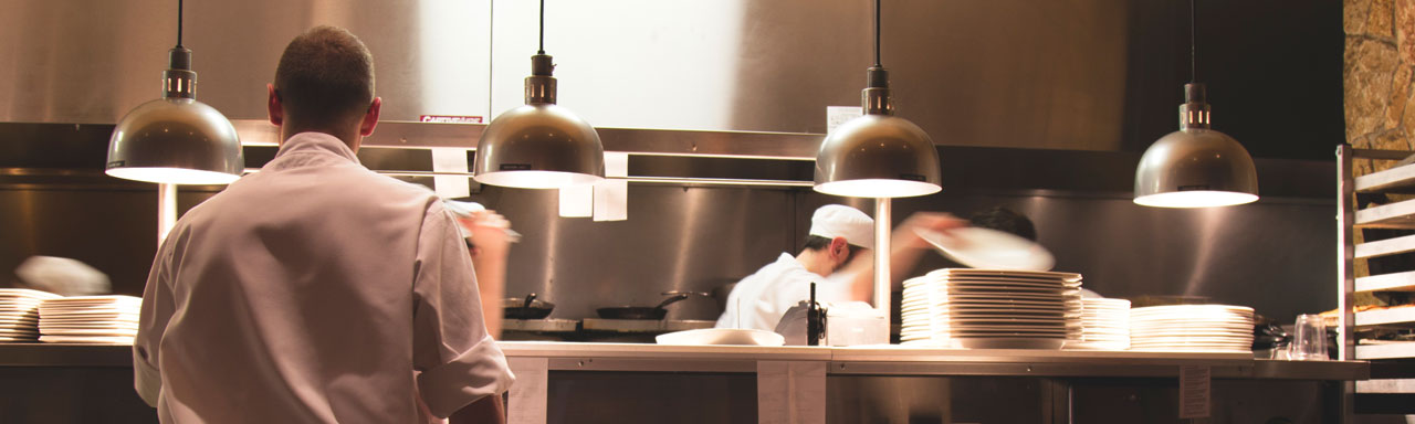 Line cooks working in an industrial kitchen.