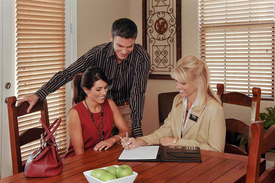 Woman and man talking to real estate agent,