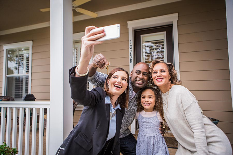 Agent taking a group photo of family who has just closed on a home purchase.