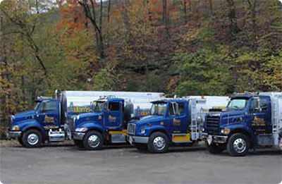 Fleet of Adams Petroleum trucks in a parking lot near the woods.