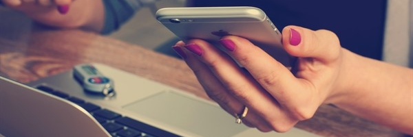 close up of a woman's hand holding an iPhone in front of a computer
