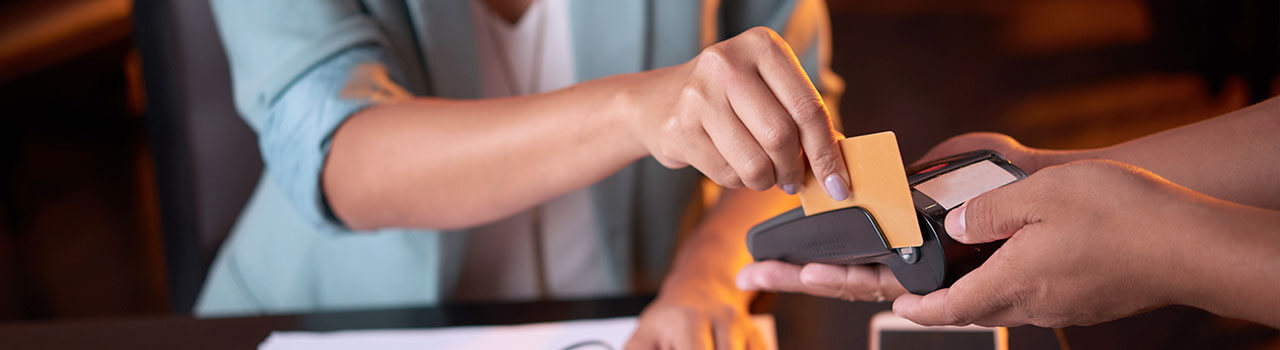 close up of a female customer swiping a credit card at a point of sale system
