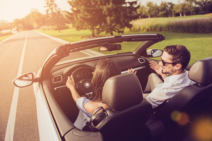 Couple driving in a convertible down a rural road.