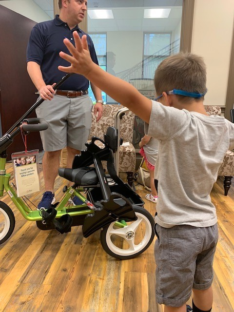 caleb receiving bike, stroller from variety the children's charity