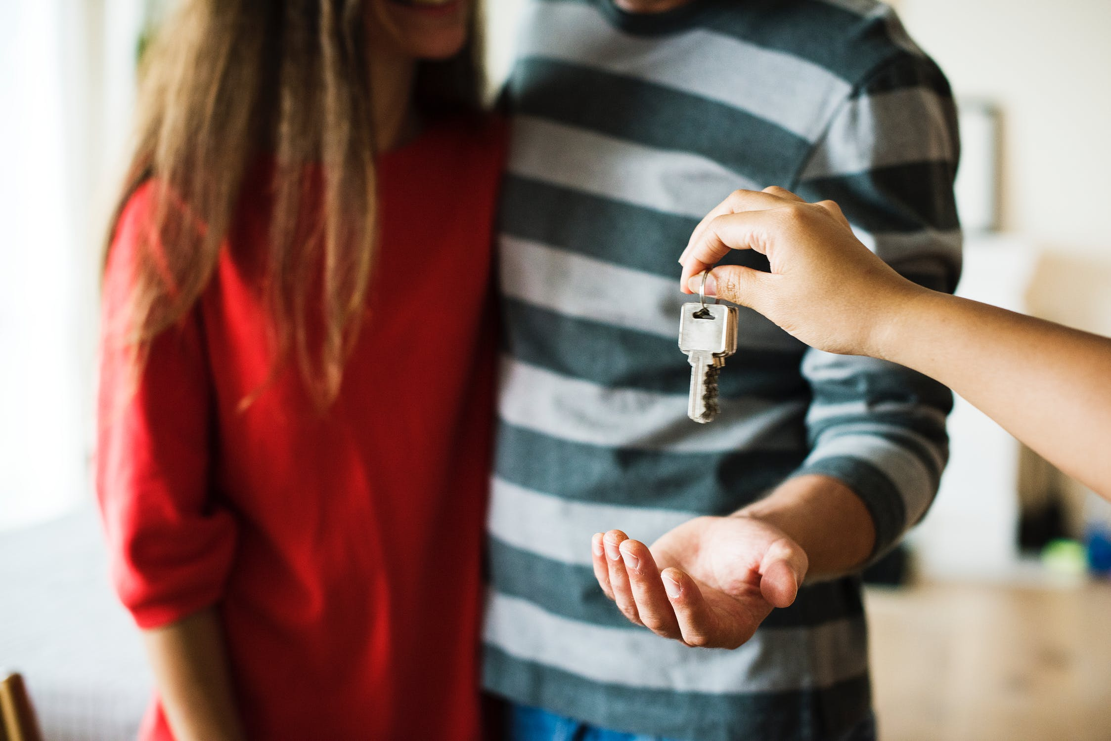 realtor handing keys to first-time homebuyers