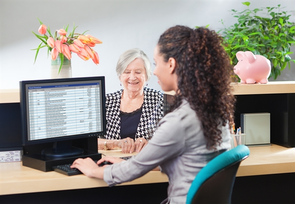 female bank employee sitting at a computer across from an elderly bank customer