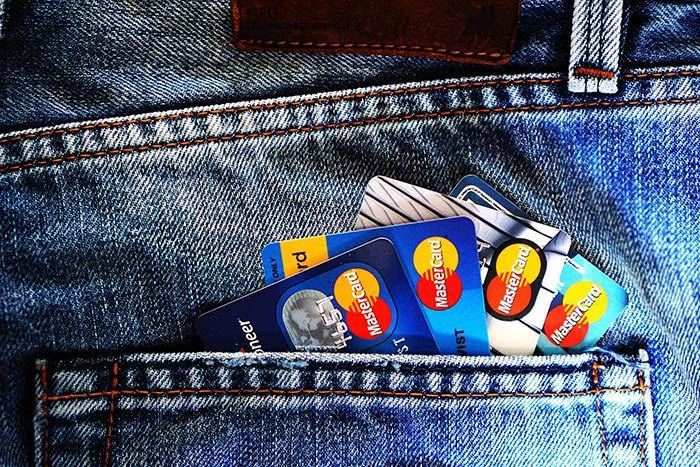 Group of credit cards lining the back pocket of a pair of jeans.