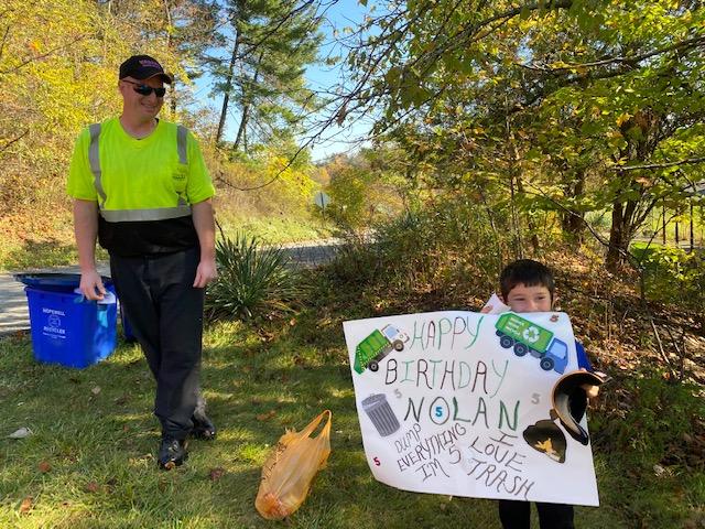 nolan holding sign next to valley waste employee
